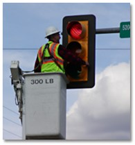 Public worker installs LED's into a traffic signal from a cherry picker.