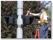 Public worker places LED's into a pedestrian signal at a cross walk.