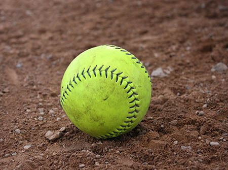 A yellow softball on a red dirt diamond