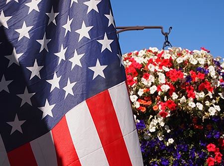 American flag with a red, blue, and white hanging basket of flowers