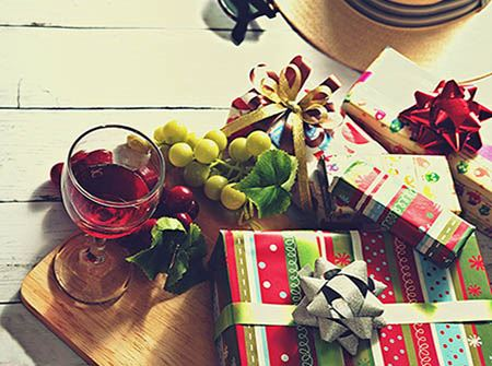Wrapped holiday gifts with a glass of wine, holly, and holiday cheer