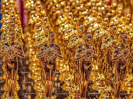Rows of gold Oscar trophies shining brightly
