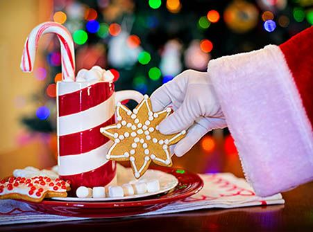 Santa Claus&#39 white gloved hand with a glass of cocoa and a cookie