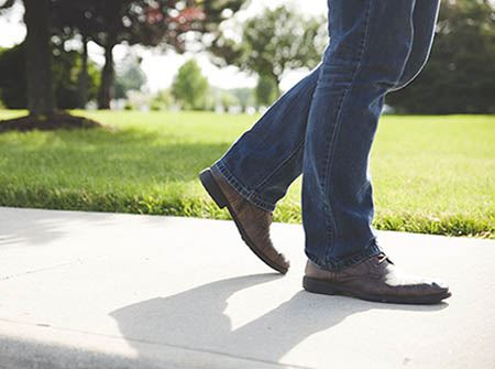 A man's legs and feet walking on a sidewalk