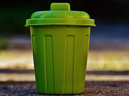A small, plastic green garbage can