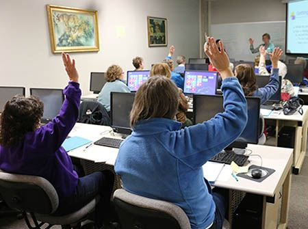 Two women sit at computers in a classroom with raised hands