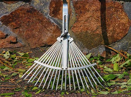 A metal rake with green leaves and branches