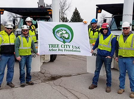 "City workers in yellow safety vests holding a white flag that says ""Tree City USA"""