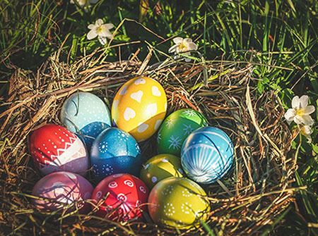 A nest of colorful Easter eggs on a green lawn