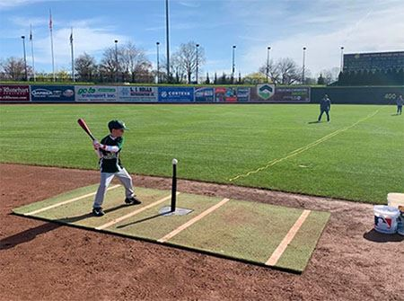 A little boy stands at a tee ready to hit a baseball into a field