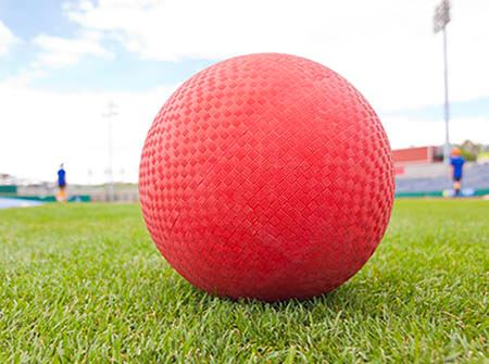 A red kick ball on green grass