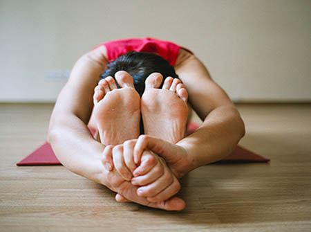 A woman's feet and hands while she stretches on a yoga mat