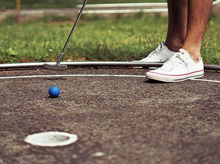 A man in white tennis shoes putts a blue ball into a mini golf hole