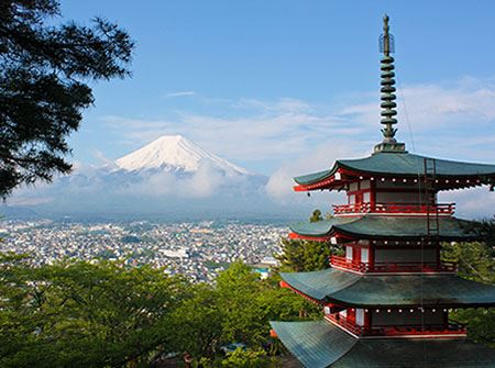A red Japanese temple with Mount Fiji in the distance