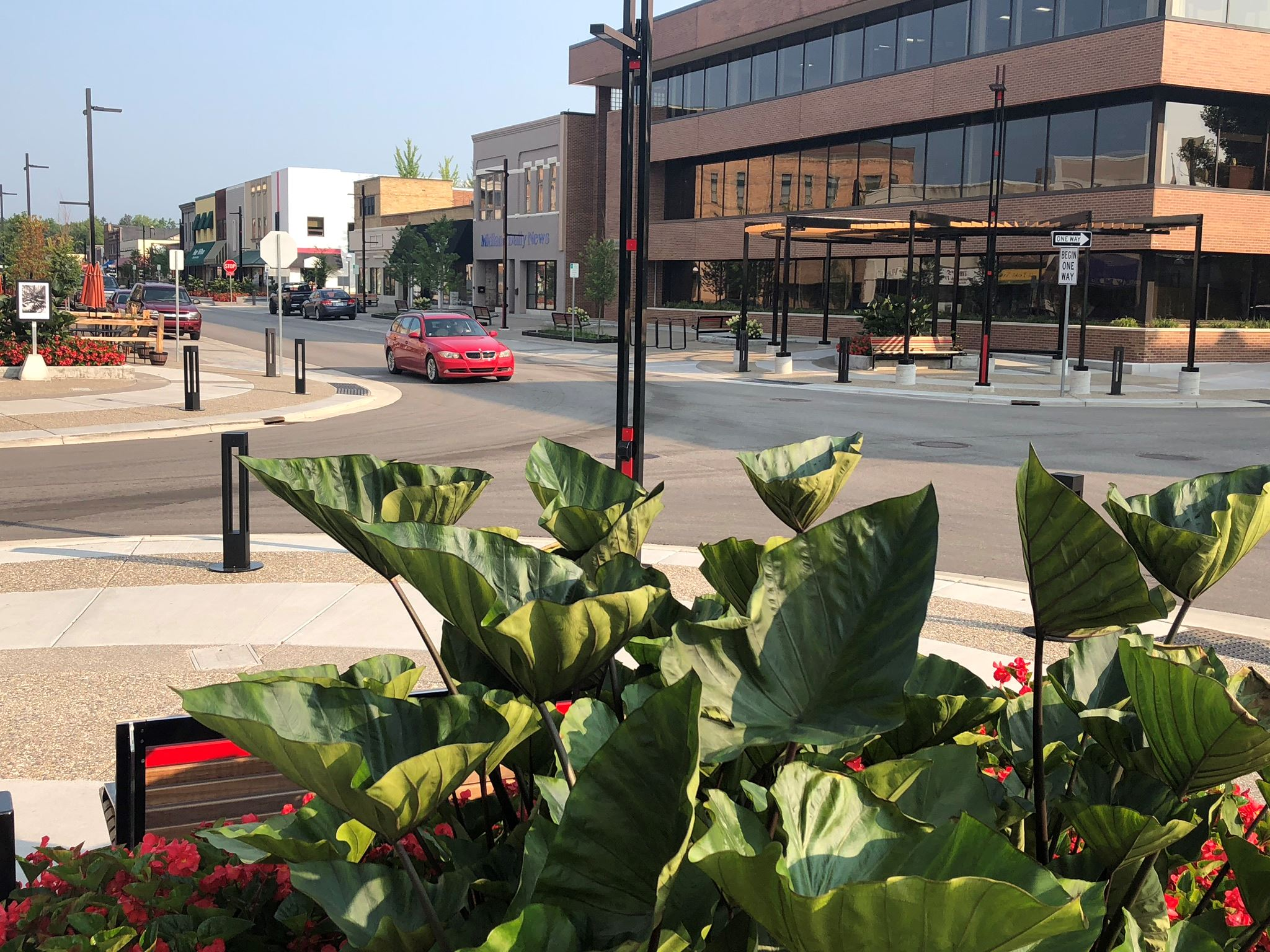 A view of downtown with red flower, a red car on the road, and brown brick