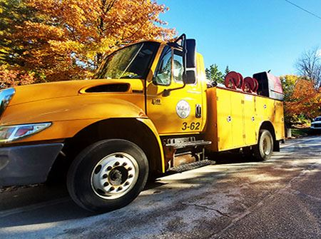 A yellow Utilities truck parked on a road with fall trees in the background
