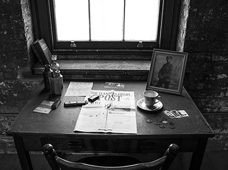 A black and white photo of a newspaper and solider's portrait on a desk