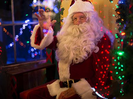 A Santa Claus in a red suit waves to the camera with green and red lights around him