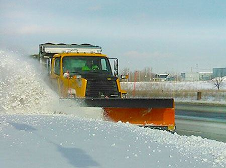A yellow City plow truck pushes snow off the road shoulder with an orange plow blade