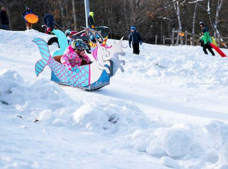 A little girl in a white and pink unicorn themed sled going down a snowy hill