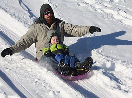 A white man and white boy sled down a snowy hill