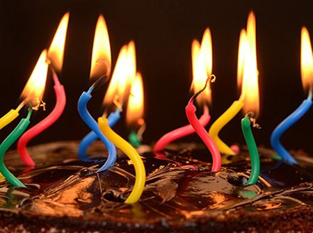 A chocolate birthday with red, blue, and other colored lit candles