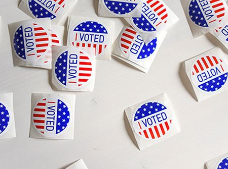 "Several red, white and blue round stickers with ""I Voted"" on them on a white background"