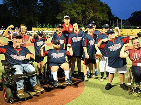 A group of Miracle League players in wheelchairs and standing flexing their arms