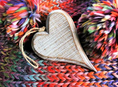 A wooden heart on a blue and red knitted blanket