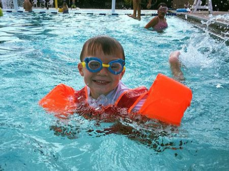 A little boy floats in a pool with orange arm bands