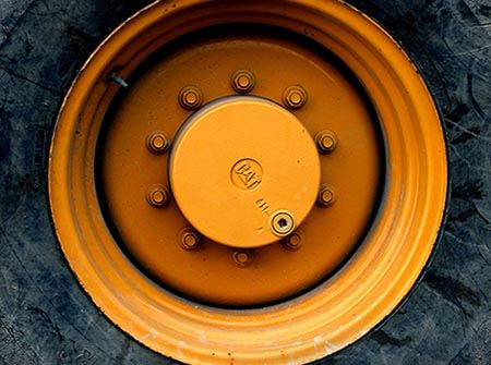 Yellow rim and black tire of a large construction vehicle
