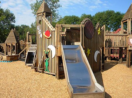 A wooden playground structure with a metal slide