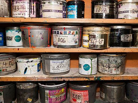 A wooden shelf with paint cans and chemical containers