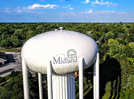 A white water tower with City of Midland logo in green and purple