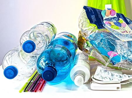 Crushed plastic bottles and other plastic materials on a white background