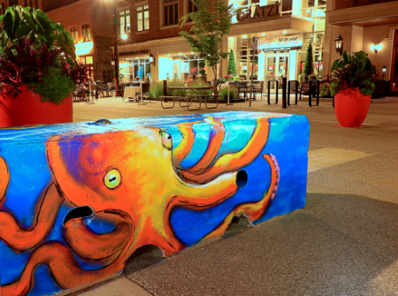 An orange octopus with a blue background is painted on a concrete barricade on a street at dark