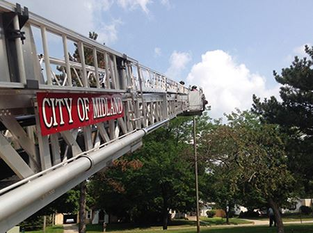 A white ladder with a red sign that says Midland Fire Department extends into the sky