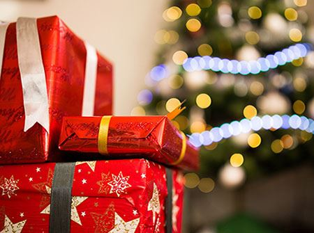 Red wrapped packages sit in front of a green lit Christmas tree