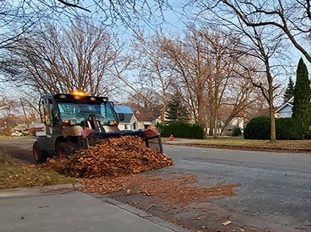 A tractor pushes orange and brown leaves down the street