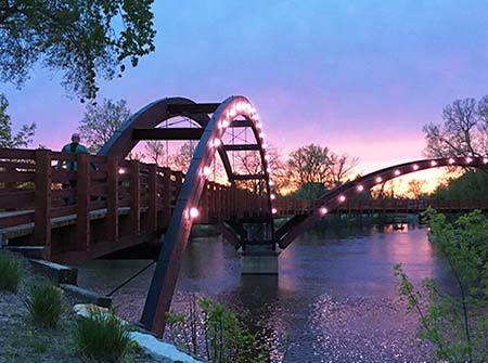 A three-legged bridge over a river with white lights against an orange and purple sunset