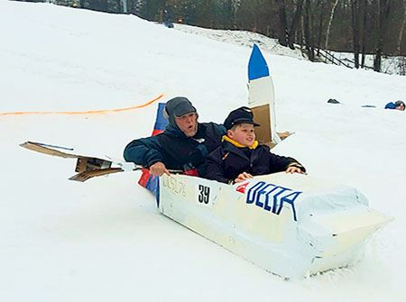 A cardboard sled that looks like a space shuttle with a young boy and a mother inside