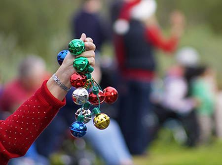 A Caucasian woman's hand holds red and green bells out into the air