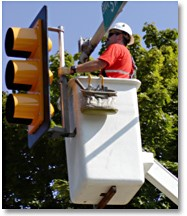 Worker maintains a traffic signal from a cherry picker.