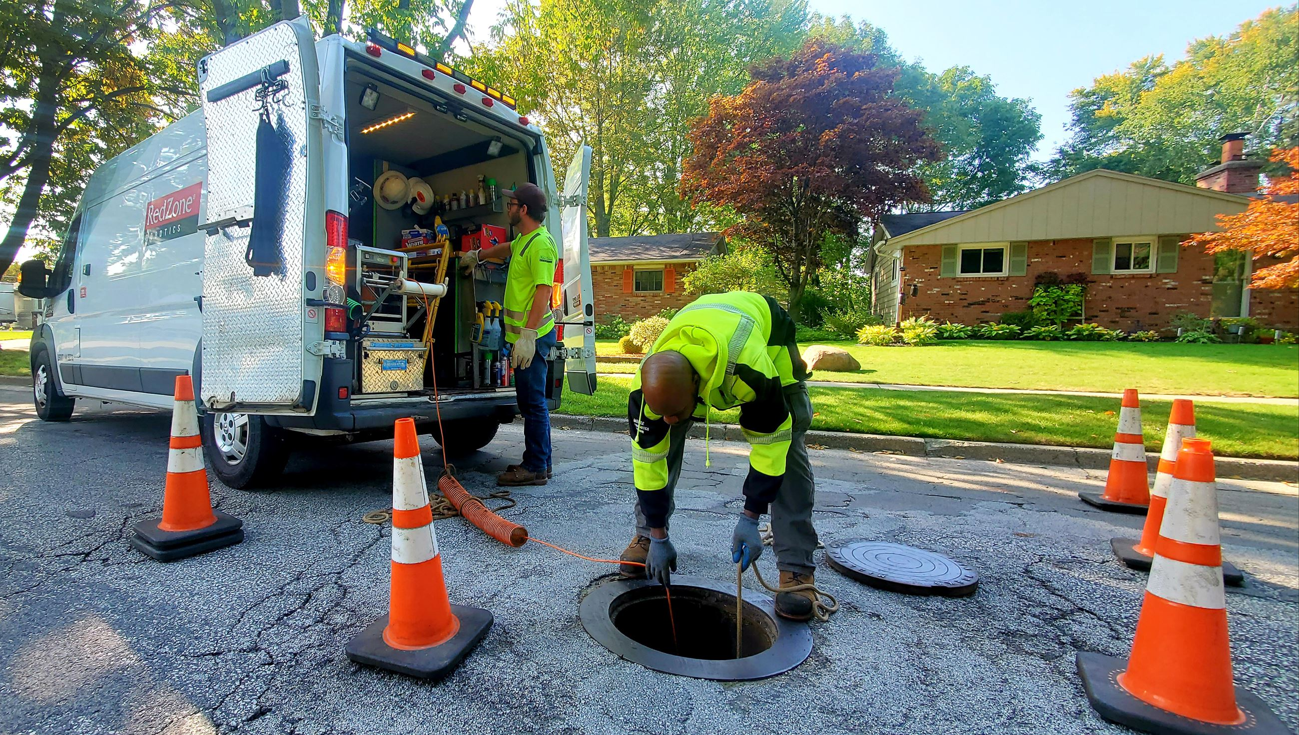 An African American man in a yellow jacket looks into a sewer manhole with a white van